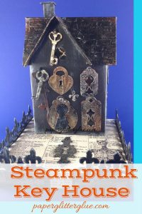 Little cardboard house decorated in steampunk style with keys and locks and keyholes