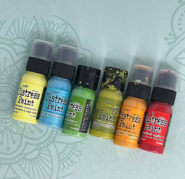 Tim Holtz Distress paint bottles showing the range of colors available