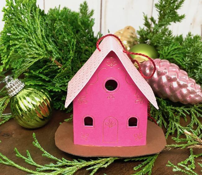 Tiny House ornament on greenery