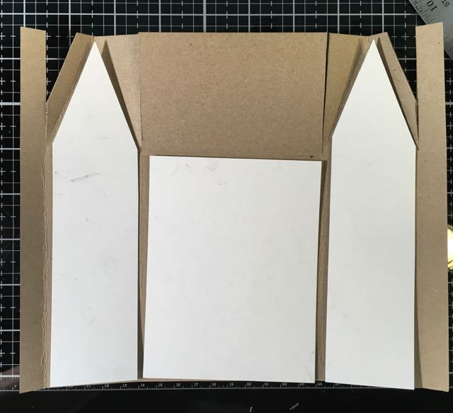 Trim reinforcement cardboard to fit the inside of the miniature house