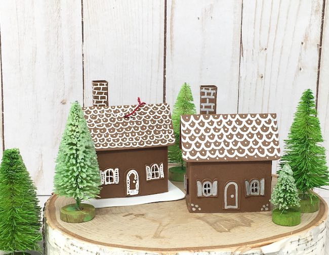Two tiny paper cottage ornaments in bottlebrush tree forest