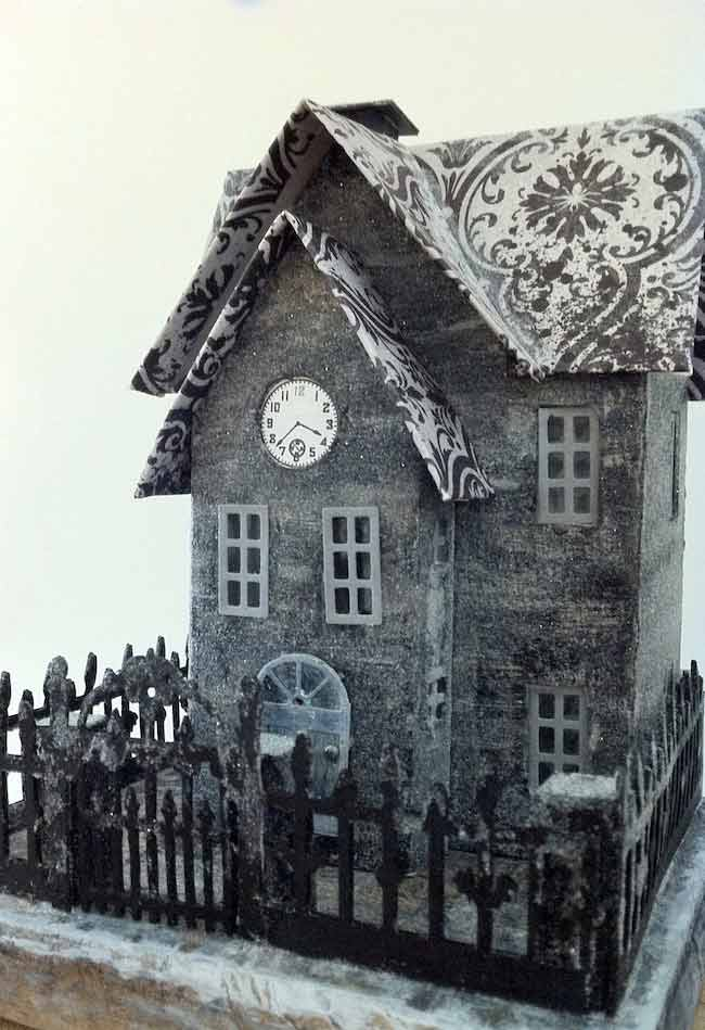 Grey and black Halloween paper house with a clock in the front gable. House is covered with a light layer of glitter