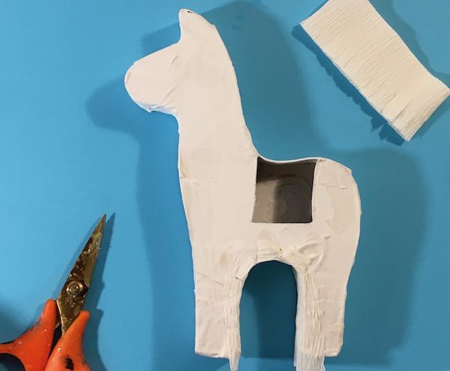 glue fringe to llama pinata form inside legs