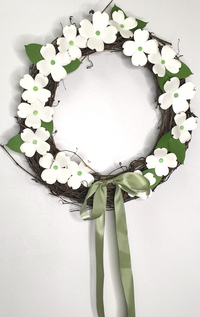 grapevine wreath decorated with dogwood paper flowers
