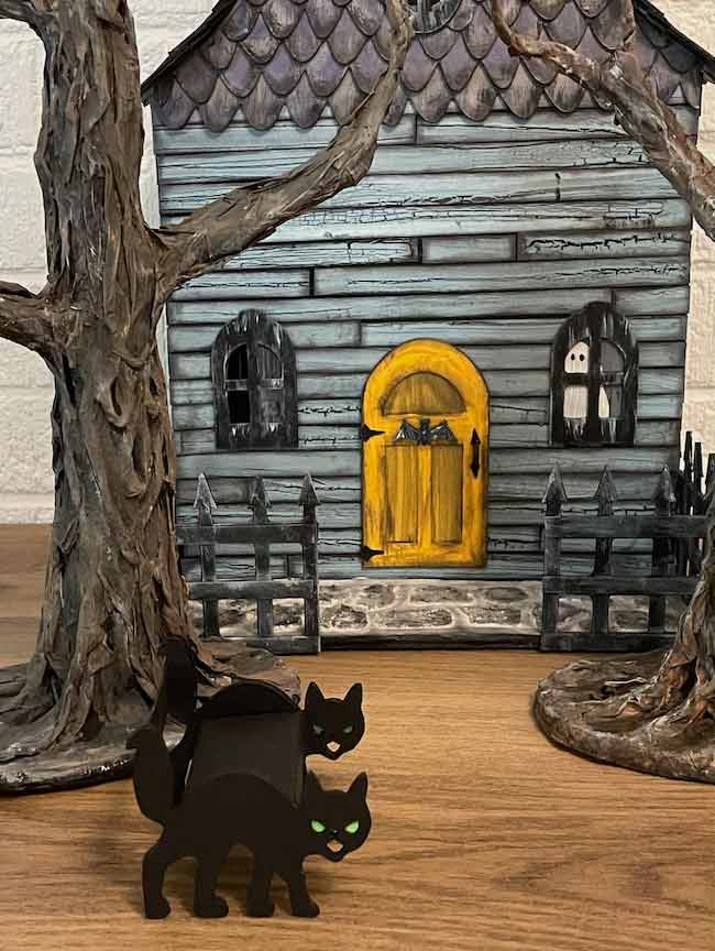larger cat bench in front of Halloween haunted dollhouse