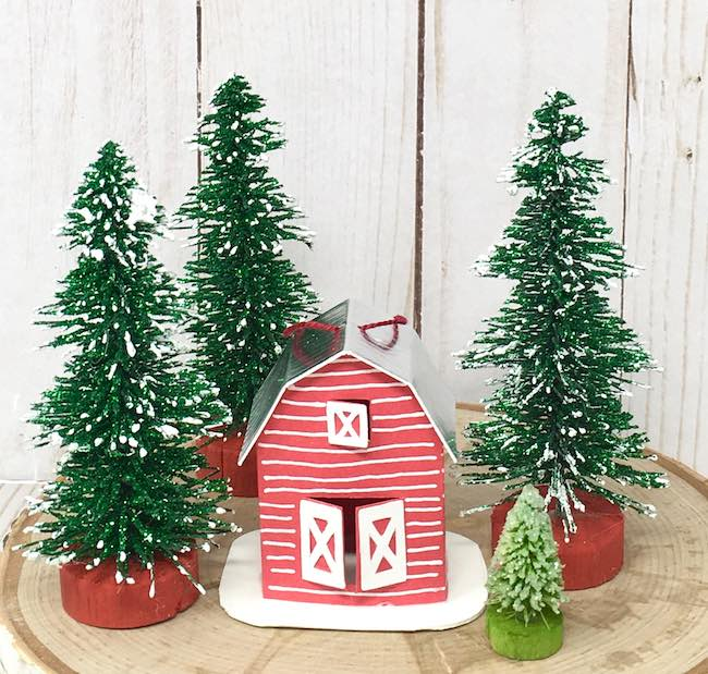 little barn ornament surrounded by trees