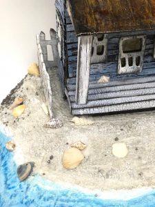 side yard of the sea worn beach house putz house with tiny seashells