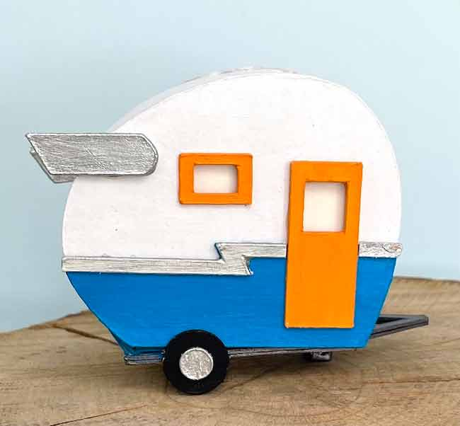 tiny paper travel trailer in teal and orange colors